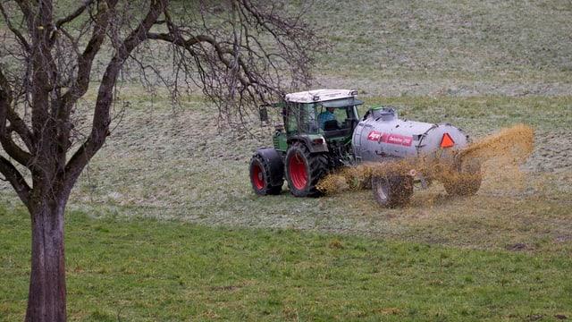 Ein Bauer mit einem Traktor verteilt Gülle auf einem Feld.