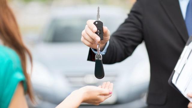 Schlüsselübergabe vor einem Auto