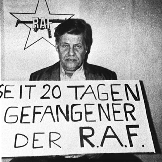 Hanns Martin Schleyer hät ein Plakat vor sich auf dem steht: «Seit 20 Tagen Gefangener der RAF». Im Hintergrund ist das Logo der RAF.