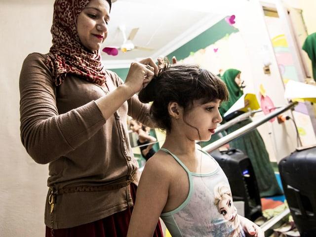 Eine Mutter macht einem Kind die Haare. Es trägt ein Tutu und Make-up.