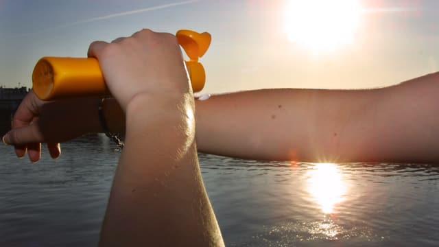 Eine Frau cremt sich den Arm mit Sonnencreme ein.