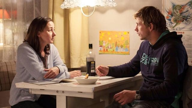 Eine Frau sitzt mit einem jüngeren Mann am Küchentisch.