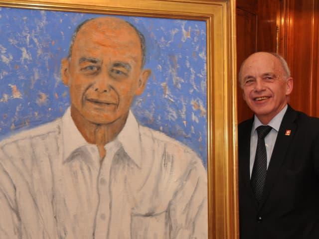 Ein Mann lächtelt in die Kamera, links neben ihm ein Gemälde von ihm.