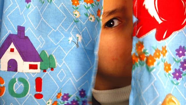 Ein autistisches Kind schaut vorsichtig hinter einem bunten Kindervorhang hervor.