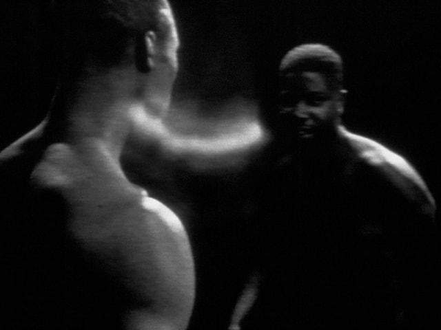 Schwarz-weiss Aufnahme von Steve McQueen, auf dem im Dunklen zwei dinkelhäutige Körper zu sehen sind, die durch einen Lichtschein verbunden zu sein scheinen.