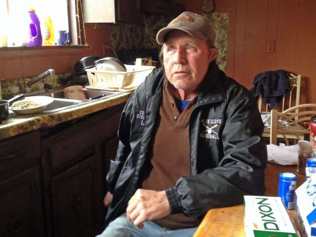 Cecil, ein älterer Mann mit Baseballkappe, sitzt an einem Holztisch.
