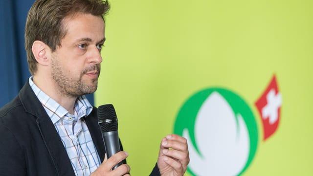 Ein Mann mit Bart und Mikrofon in der Hand steht vor dem Bio Suisse Logo.