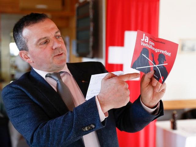Walter Wobmann mit Flyer für ein Verhüllungsverbot