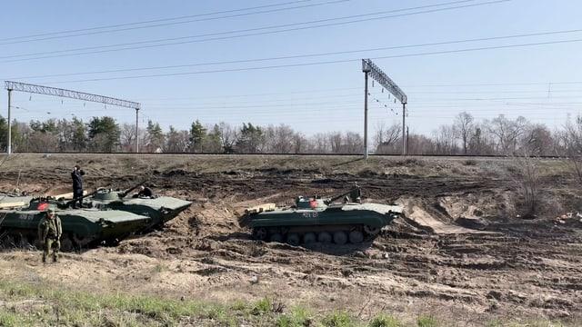 Mehrere russische Panzer stehen hintereinander neben Bahngeleisen