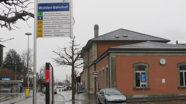 Bahnhofsgebäude in Wohlen, im Vordergrund Bus-Schild
