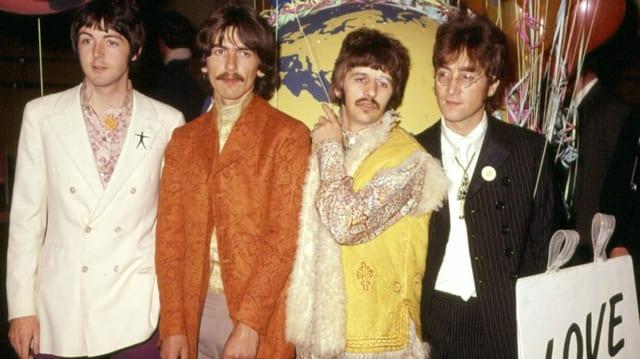 ein Foto von vier bunt angezogenen Männern