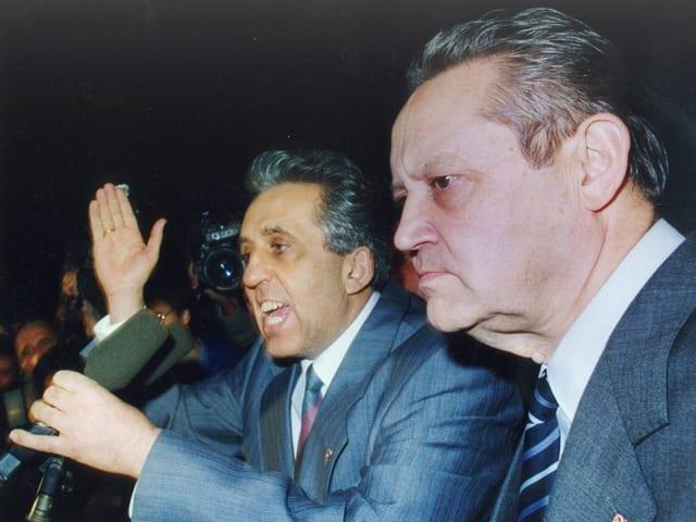 Zwei Männer sprechen zu Demonstranten.