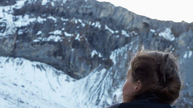 Ein Frauenkopf, man sieht ihn von hinten, bestaunt eine eisige Felswand.