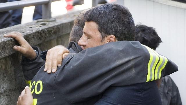 Premier Matteo Renzi umarmt einen Helfer.