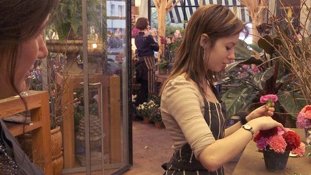 Eine Frau sortiert Blumen.