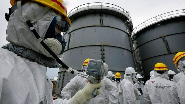 Spezialisten in weissen Schutzanzügen messen die Umgebungs-Radioaktivität im japanischen Kernkraftwerk Dai-ichi in Fukushima.