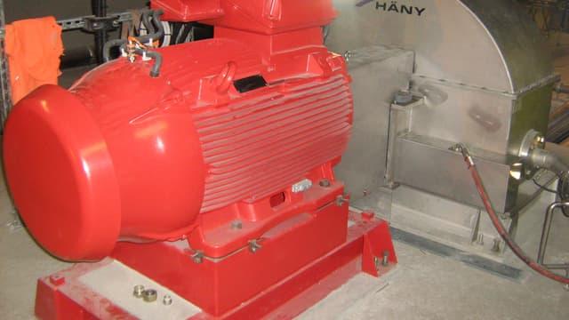 Eine silberfarbene Turbine und ein roter Generator in der Tiefe des Gotthard-Basistunnels.