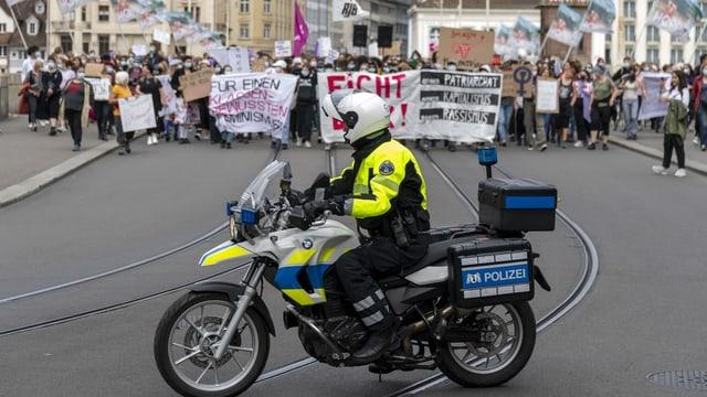Motorfahrzeug der Polizei. Im Hintergrund Demonstrationsteilnehmerinnen.