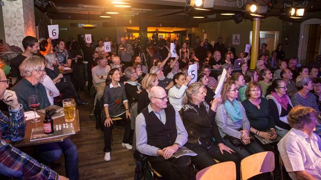 Publikum mit Tafeln, auf denen Schulnoten stehen