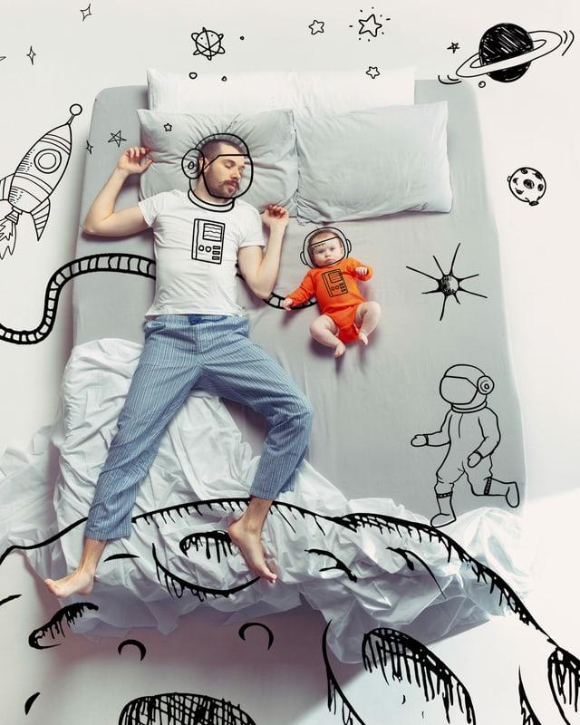 Ein Mann und sein kleines Kind schlafen im Bett.