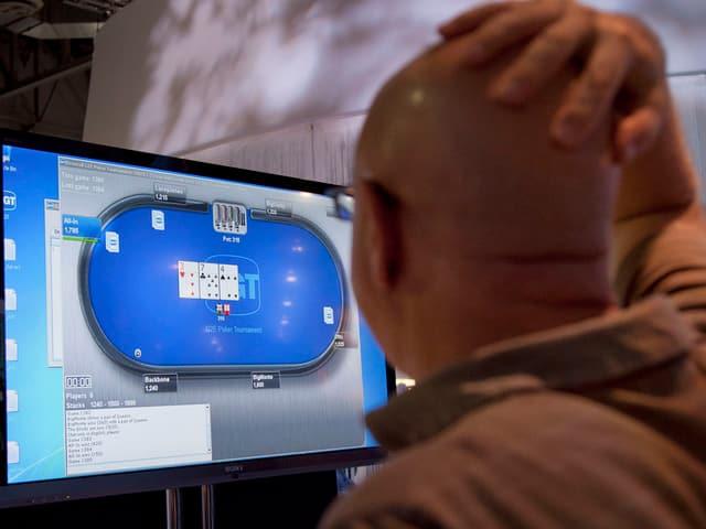 Ein Mann steht erregt vor einem Monitor, der ein Pokerspiel zeigt.