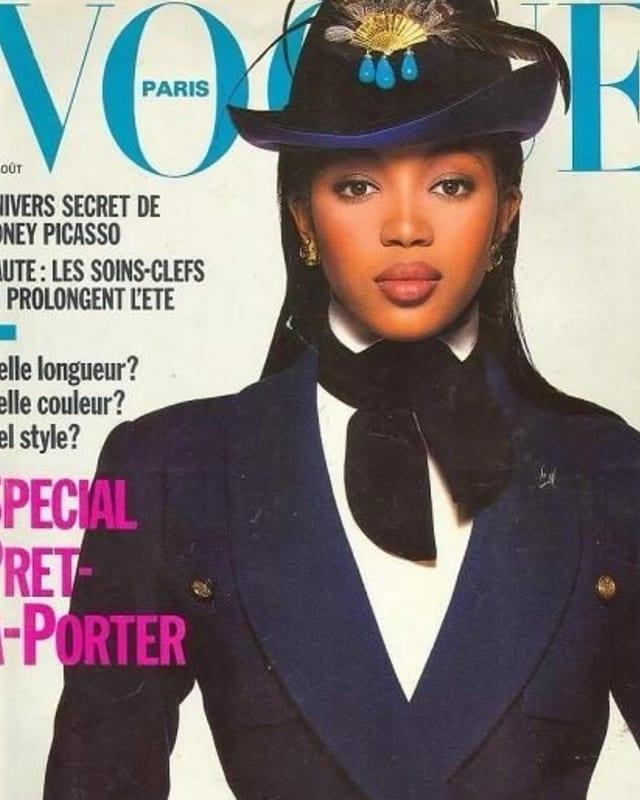 Vogue-Cover mit Naomi Campbell. Sie trägt eine Art dunkelblaue Uniform mit Jägerhut und schaut direkt in die Kamera.
