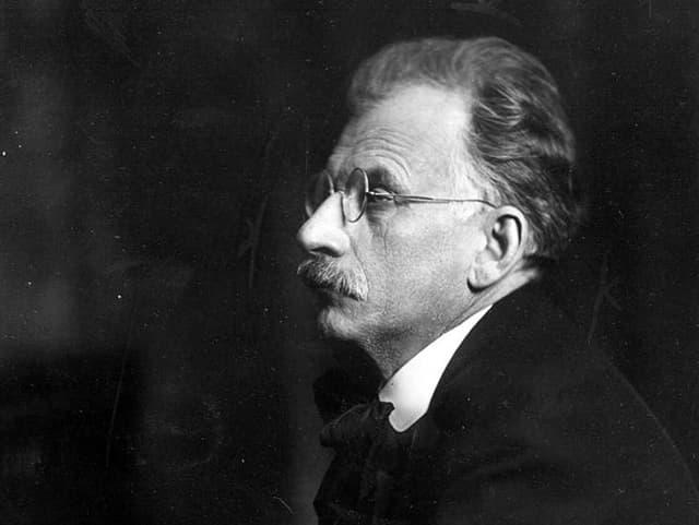 Ein Schwarz-Weiss-Porträt eines ernsten Mannes mit Schnauz und Brille.