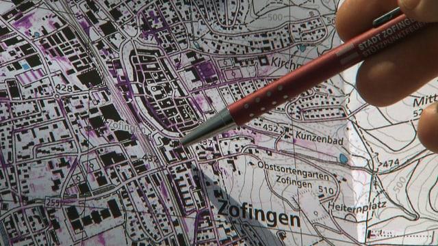 Karte mit lila Stellen, zu sehen ist die Altstadt von Zofingen. Daneben zeigt jemand mit einem Kugelschreiber auf die Karte.