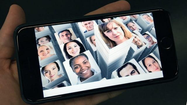 Eine Hand hält ein Smartphone. Darauf ist ein Foto mit sehr vielen Menschen.