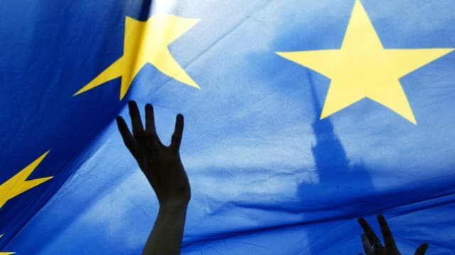Eine grosse Europa-Fahne, wird von Händen in die Höhe gehalten.