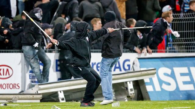 Ein Aarauer Hooligan wirft Fanenstangen gegen die Basler Hooligans nach dem Meisterschaftsspiel 2014.