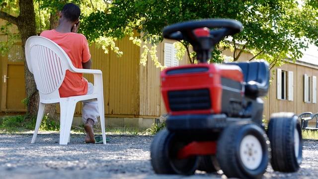 Im Vordergrund unscharf ein Spielzeugtraktor, im Hintergrund sitzt ein Flüchtling auf einem Plastikstuhl und telefoniert.