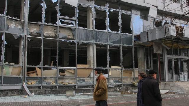 Ein völlig zerschossenes Gebäude, davor mehrere Zivilisten.