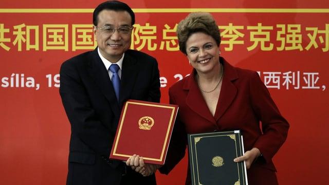 Li Keqiang und Dilma Roussef stehen mit je einem Dossier in der Hand vor einer roten Waand mit chinesischen Schriftzeichen und lachen in die Kamera.