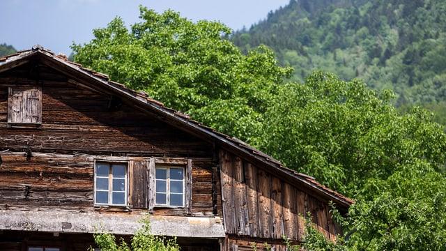 Kleine Fenster, dunkles Holz: Das rund 700-jährige Holzhaus an der Lauigasse in Steinen mit Bäumen im Hintergrund.