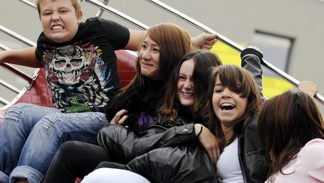 Fünf Jugendliche auf einen Bahn auf einer Messebahn: Drei Mädchen lachen, ein Junge verzieht das Gesicht und eine Person schaut weg.