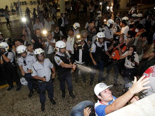 Polizisten und Demonstranten Auge in Auge, ein Polizist sprüht Pfefferspray in Richtung Protestierende.