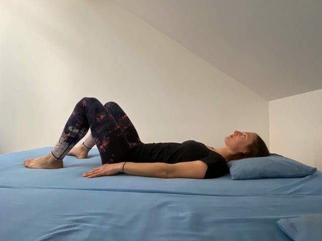 Frau liegt auf Bett auf Rücken.