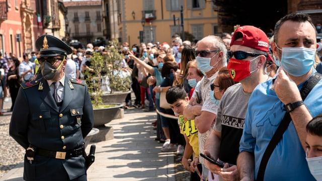Menschenauflauf, viele tragen eine Gesichtsmaske, darunter auch ein Polizist.