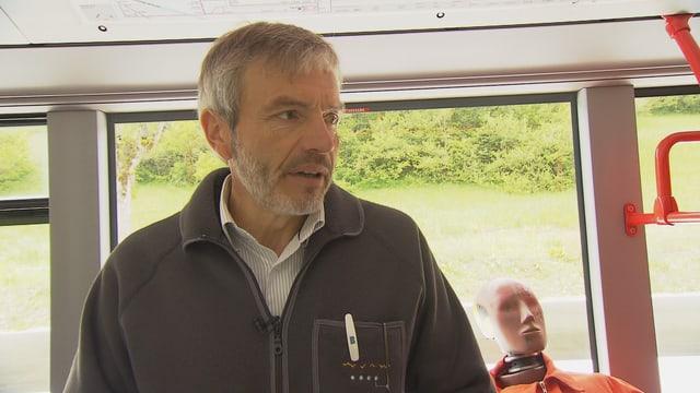Bernhard Gerster, Experte für Fahrzeugsicherheit, mit einem Dummy für Crashtests im Hintergrund.