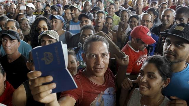 Eine risige Menschenmenge, vorne ein Mann, der einen kubanischen Pass hochhält.
