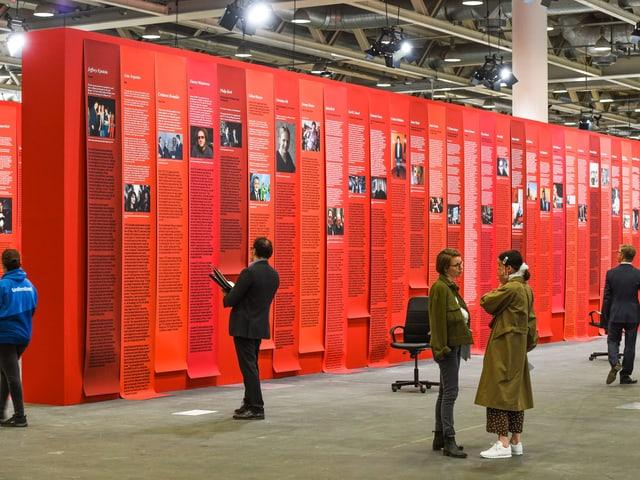 Menschen stehen vor einer roten Wand mit Texten