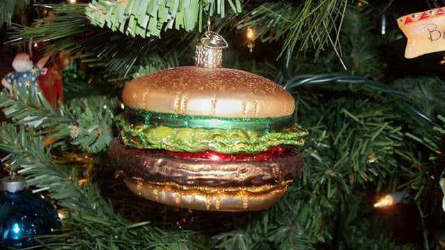 Eine Christbaumkugel in Form eines Hamburgers dient als glitzerndes Christbaumornament.