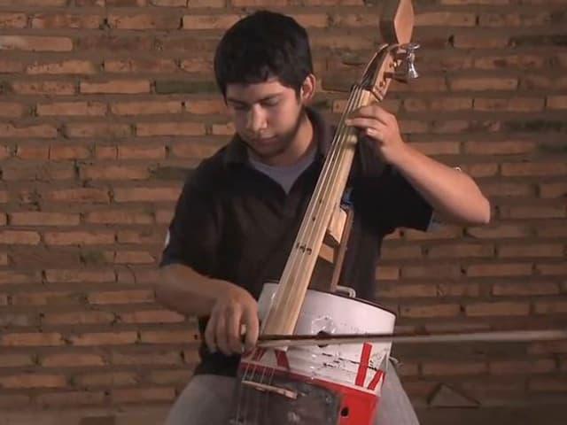 Ein Junge spielt auf einem Cello, das aus einem Ölkanister und weiterem Abfall gebaut ist.