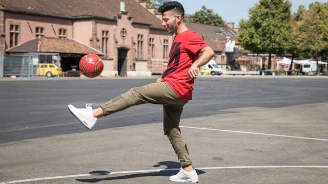 Ein junger Mann spielt Fussball auf einem Platz