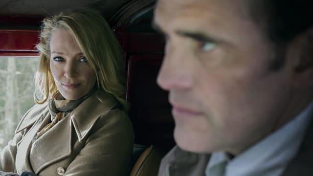 Eine Frau und ein Mann nebeneinander in einem Auto.