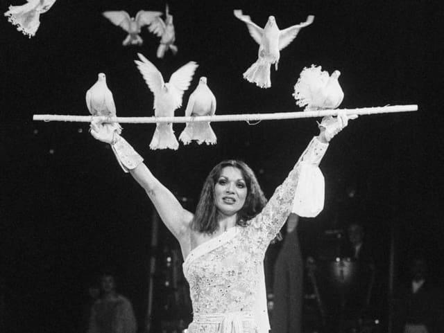 Eine Frau mit einer Stange in der Hand, auf der Tauben sitzen.