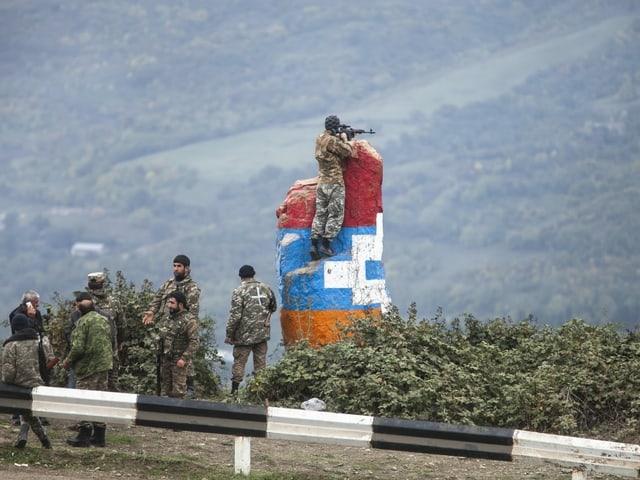 Ein Sniper beobachtet das Gebiet in der Nähe von Hadrut, er steht auf einem farbigen Felsen.