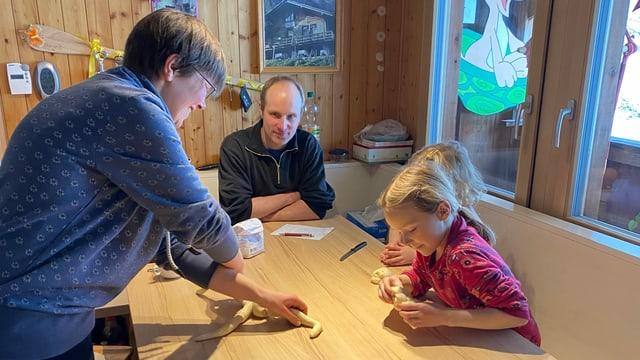 Ehepaar Rauber am backen am Familientisch mit den beiden Töchtern.
