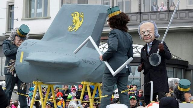 Ein als Maurer verkleideter Fasnächtler präsentiert ein Kampfflugzeug.